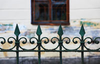 The old metal city fence with sharp points is painted on top with green paint, which is flaky
