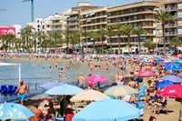 Torrevieja, Spain - June 10, 2019: Crowd of tourists people spend time on the Playa Del Cura sandy beach in Torrevieja resort city, high rise building palm trees, sunny day. Costa Blanca, Spain