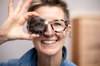 woman with glasses looking through tinted glass