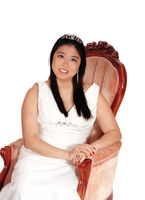 Happy bride sitting in an old armchair, smiling and relaxing