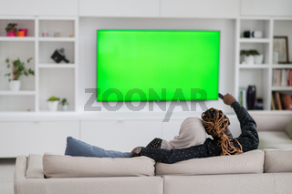 African Couple Sitting On Sofa Watching TV Together