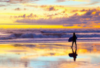 surfer walking sunset Bali beach