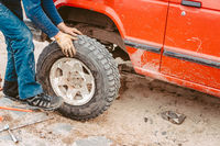 Man rolls a new replacement wheel to 4x4 off road truck