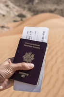 Passport and Business Boarding Pass with desert as background