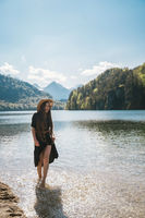 The girl in the dress and hat of the lake in the mountains