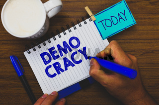 Word writing text Demo Cracy. Business concept for freedom of the people to express their feelings and beliefs Man holding marker notebook clothespin reminder wooden table cup coffee.