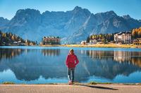 Woman on the coast of Misurina lake at sunrise in autumn