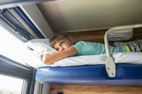 An eight-year-old girl lies on the top shelf of a reserved seat car and looks tiredly out the window