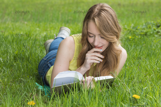 Girl reading book on grass