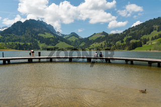 Schwarzsee, FR / Switzerland - 1 June 2019: tourists enjoy the summer lakeside view at the Schwarzsee Lake in the Swiss Alps in canton Fribourg