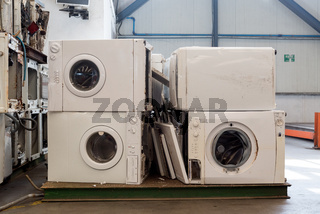 Piles of used and thrown away washing machines waiting to be recycled on a recycling plant site