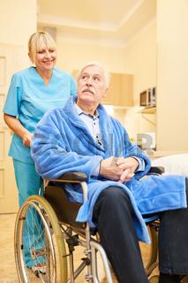 Senior als Patient im Rollstuhl mit Pflegekraft
