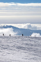 Silhouettes of skiers and snowboarders on snowy ski slope and mountains