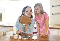 Cute smiling mother and daughter applying face cream