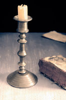 Vintage candle holder and an old book