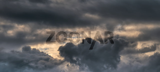 Panoramic shot of the autumn sky with huge heavy clouds of gray-blue color and the rays of the sun.