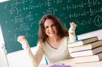Young female math teacher in front of chalkboard