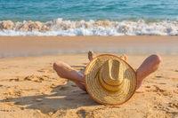 Young male tourist sunbathing on sea beach
