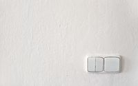 Old light switches on white wall freshly painted, some drops of paint over plastic