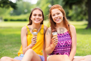 teenage girls eating ice cream at picnic in park