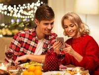 couple with smartphone at home christmas dinner