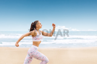 Young athlete woman jogging on the sea beach. Running on sand along water