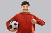 male football fan with soccer ball shows thumbs up