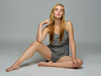 beautiful woman in short overall is sitting on the floor