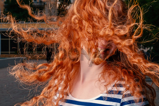 Faceless shot of red haired girl with her curly hair fly in air while she shaking her head