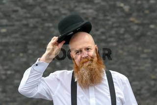 Polite bald bearded man doffing his hat
