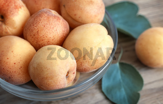 Ripe apricots in a glass vase.