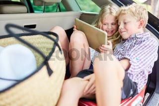 Zwei Kinder im Auto mit Tablet Computer