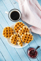 Tasty sweet waffles with raspberry jam and tea cup.