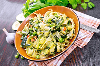 Tagliatelle with green vegetables on dark board