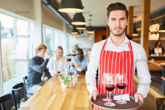 Junger Kellner serviert Wein auf einem Tablett