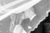 Bride and groom kisses tenderly in the shadow of a flying veil. Artistic black and white wedding photo.