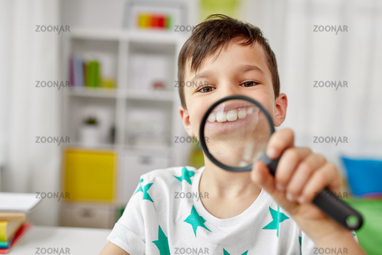 boy with magnifier showing big teeth at home