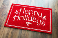 Happy Holidays Christmas Red Welcome Mat On Wood Floor Background