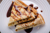 Flat lay French crepes with chocolate sauce in ceramic dish on wooden kitchen table