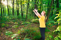 Happy woman outstretching hands to sun