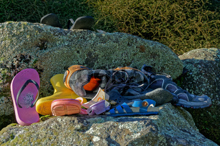 A pile of abandoned or lost shoes and assorted footwear