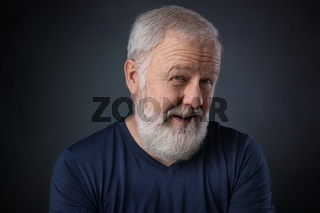 Elderly man with beard looking skeptical