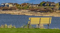 Panorama Bench with a scenic view of lake and snow capped mountain against blue sky