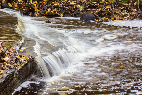 Small waterfall in a stream with autumn leaves