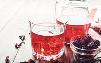 Closeup view at glass of hibiscus ice tea and jug on wooden table background