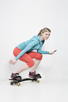 Young woman casually stands on a snakeboard
