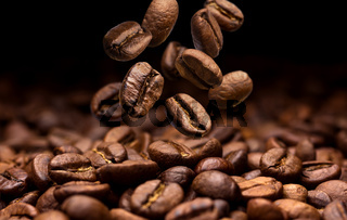 Falling coffee beans. Dark background with copy space