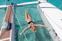 Woman relaxing on a summer sailing cruise,lying in hammock of luxury catamaran near picture perfect white sandy beach on Spargi island in Maddalena Archipelago, Sardinia, Italy.
