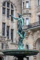 Ornate statue of Woman in fountain with building in background