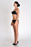 woman  full length figure from  three-quarters angle in underwear.